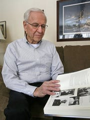 """In this 2016 photo, Korean War veteran Glenn Dohrmann looks through a book about the war called """"Devotion."""" Dohrmann was nominated for a Medal of Honor for his heroism as a rifle platoon leader in Korea."""