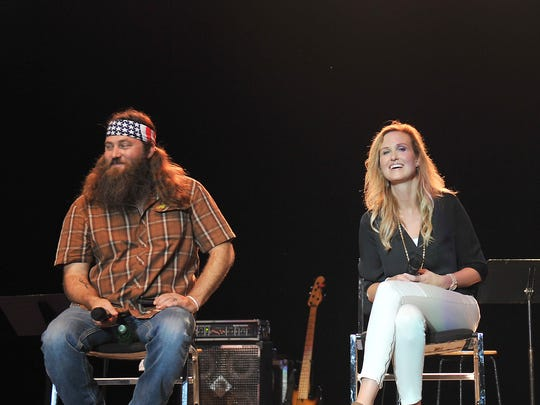 "Members of the ""Duck Dynasty"" on stage at the Iowa State Fair Grandstand, left to right: Willie Robertson , Korie Robertson and Si Robertson, Sunday August 10, 2014 in Des Moines, Iowa."
