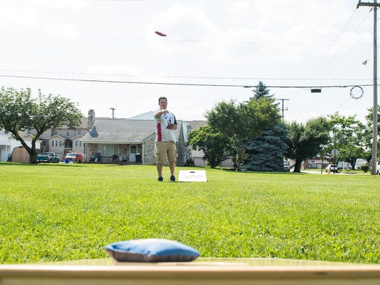 Mike Rabine plays a round of cornhole at Moul Field