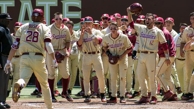 Dylan Busby celebrates after hitting a grand slam in FSU 16-5 series-clinching win over Louisville on Sunday.