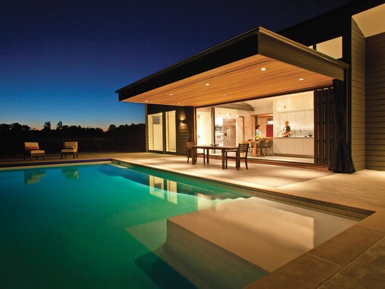A wall of windows overlooking a tranquil pool provides