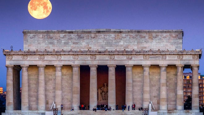 The full moon sets behind the Lincoln Memorial as people line the steps to watch the sun come up across the other end of the National Mall in Washington on March 31, 2018.