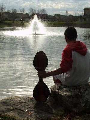 Christopher Caruthers pauses from skateboarding to ponder the fountain.