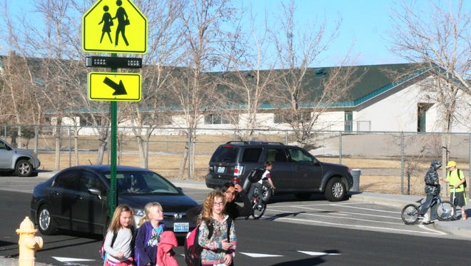 A group of Sutro Elementary School students waits to cross the street as traffic stops for the new flashing crosswalk beacons installed near the school by Lyon County public works.