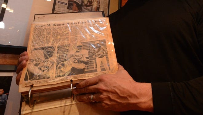 Bryan LeCompte holds his scrapbook from the 1983 James M. Bennett High School football team, the year the Clippers won the state championship. On the first page is an article about Wardell Turner, who was killed in Afghanistan.