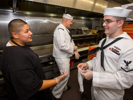 La Posta restaurant kitchen supervisor Nichole Arrelano instructs Culinary Specialist First Class Charles Johnson, center, and Culinary Specialist Third Class Jordan Prince, right, on the cooking techniques of the restaurant. Johnson and Prince, who both cook on the submarine USS New Mexico, were there to learn the recipes of the restaurant so they can serve New Mexico cuisine to the 130 sailors onboard.