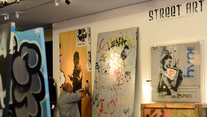 """A man points his cellphone toward streetartist Banksy's aerosol stencils of """"Umbrella Rat"""" (center), seen between 'Black Bobby' (left) and """"TV Girl"""" (right), on display amid preparations at Julien's Auction House in Beverly Hills, Calif., on December 4, 2013,"""