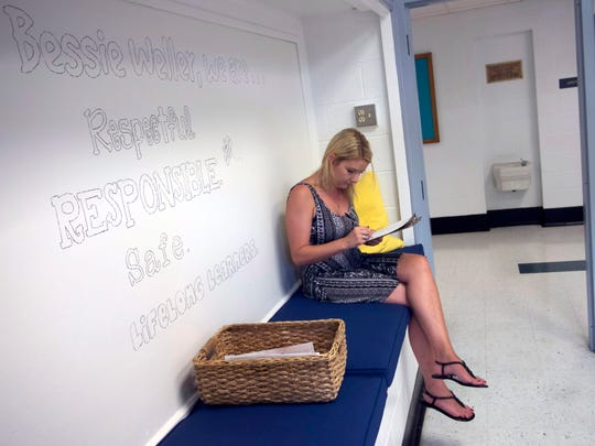 Brittany Wills fills out paperwork to sign up her son Riley Mason for Kindergarten Tuesday, August 11, 2015. She is sitting on a new bench in the main lobby that has been renovated this year to make the main entrance more welcoming and user-friendly.   They have renovated the main entrence to make it more welcomeing. This new window to the office is part of  making the staff more accesable for parents and visitors.