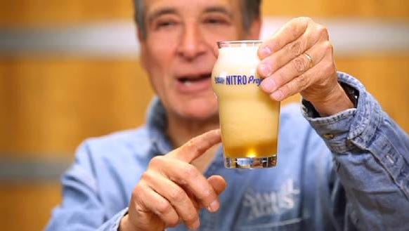 Boston Beer Co. Founder and Chairman Jim Koch holding a just-poured Samuel Adams Nitro White Ale.
