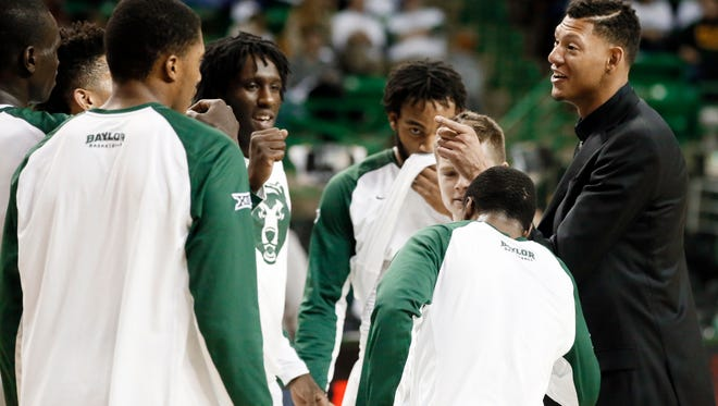 In this photo taken Jan. 14, 2015, Baylor student assistant Isaiah Austin, right, talks to the team before an NCAA college basketball game against Iowa State in Waco, Texas.
