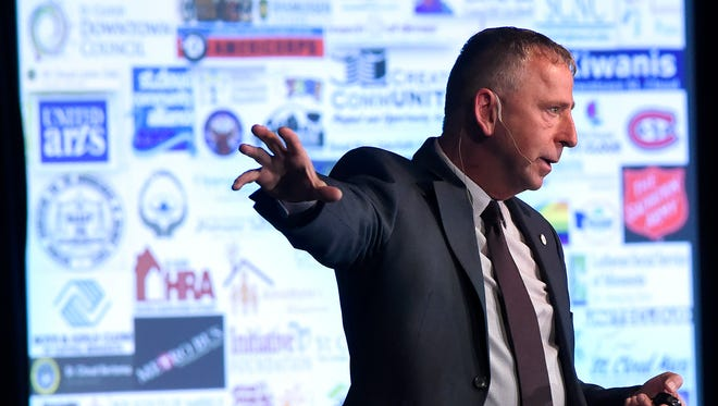 St. Cloud Mayor Dave Kleis gives his State of the City presentation with logos of local organizations in the background Thursday at the River's Edge Convention Center.