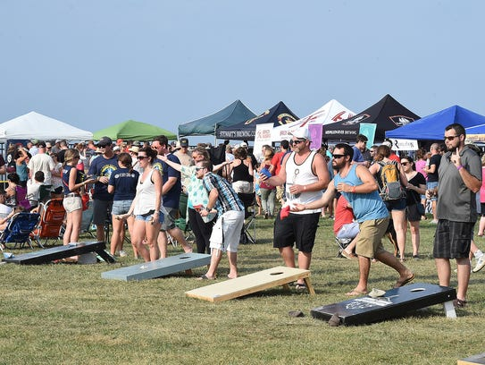Beer-drinkers play cornhole at last year's  at Brews