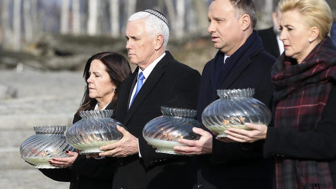 United States Vice President Mike Pence and his wife Karen Pence, left, walk with Poland's President Andrzej Duda and his wife Agata Kornhauser-Duda, right, with lights in their hands during their visit at the Nazi concentration camp Auschwitz-Birkenau in Oswiecim, Poland, Feb. 15, 2019.