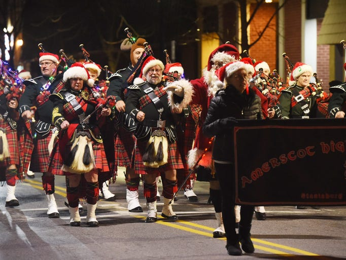 Members of the Amerscot Highland Pipe Band march in