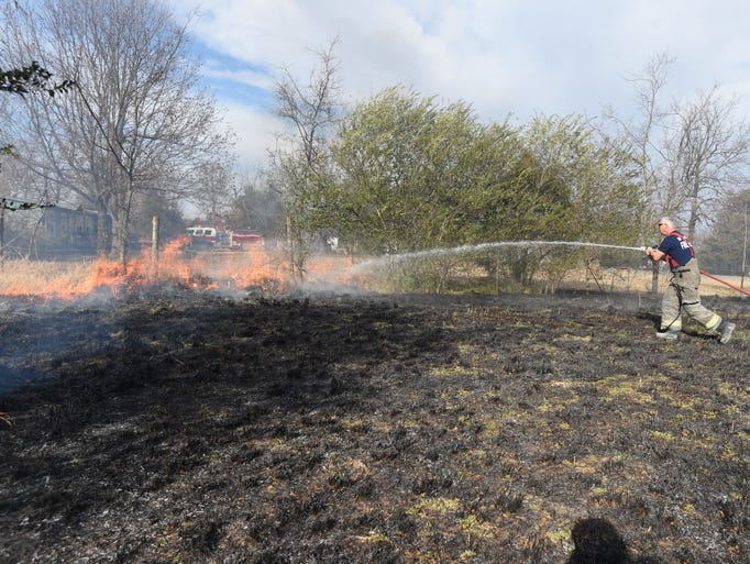 A firefighter puts out a hot spot Monday on Old Military