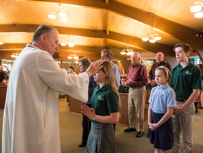 Josefine Tayman, 11, receives ashes from Eucharistic