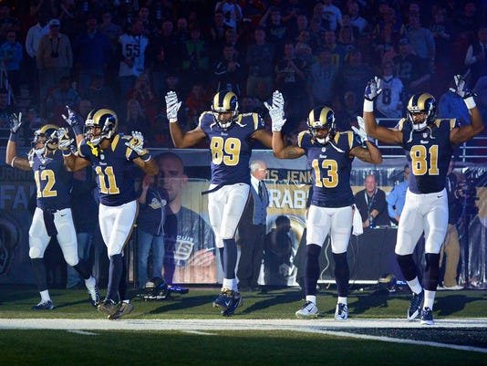 St. Louis Rams players hold up their hands before game against the Oakland Raiders