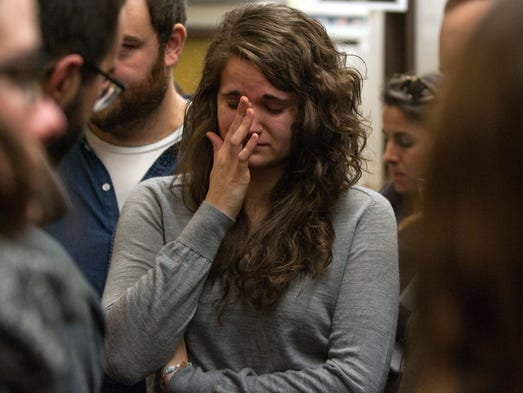 A student weeps in front of the office of her former