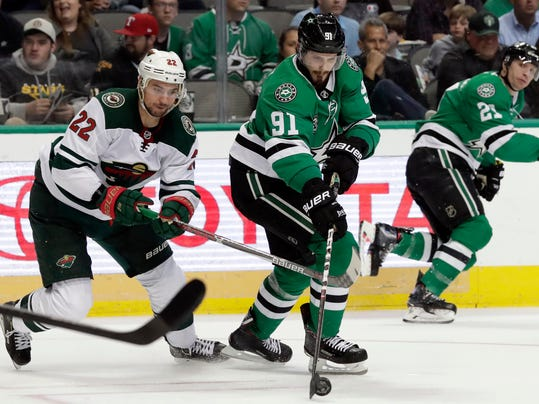 Dallas Stars center Tyler Seguin (91) prepares to pass the puck under pressure from Minnesota Wild right wing Nino Niederreiter (22) in the second period of an NHL hockey game in Dallas, Saturday, March 31, 2018. (AP Photo/Tony Gutierrez)