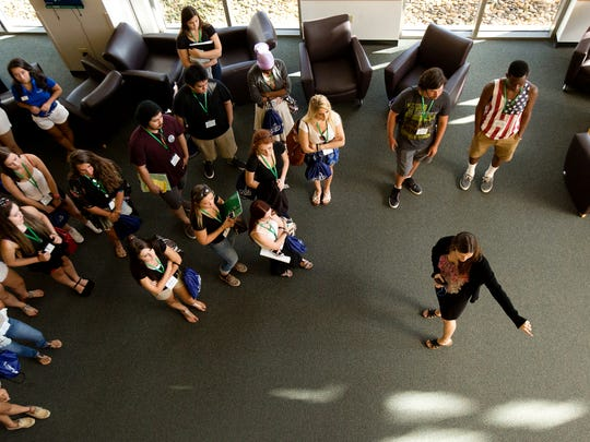 Incoming Florida Gulf Coast University freshman get a tour of the campus during their orientation on Monday, July 14.  Giving them information about the library is Heather Snapp, a first year experience/outreach librarian.  In the far back are students and orientation guides.