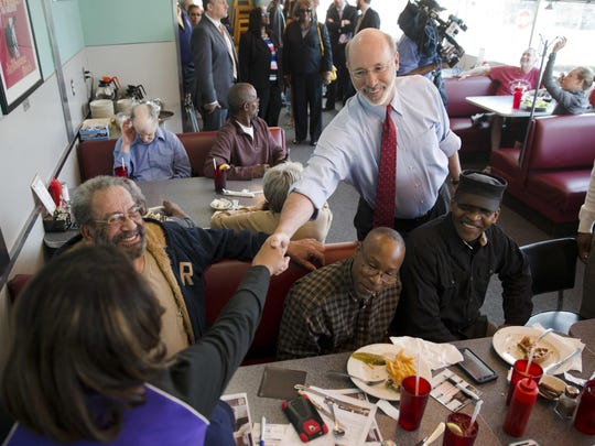 In this March 8, 2016, file photo, Pennsylvania Gov. Tom Wolf meets with diner patrons before discussing his executive order to increase the minimum wage for state government employees and workers on jobs contracted by the state, during a news conference at the Trolley Car Cafe in Philadelphia.