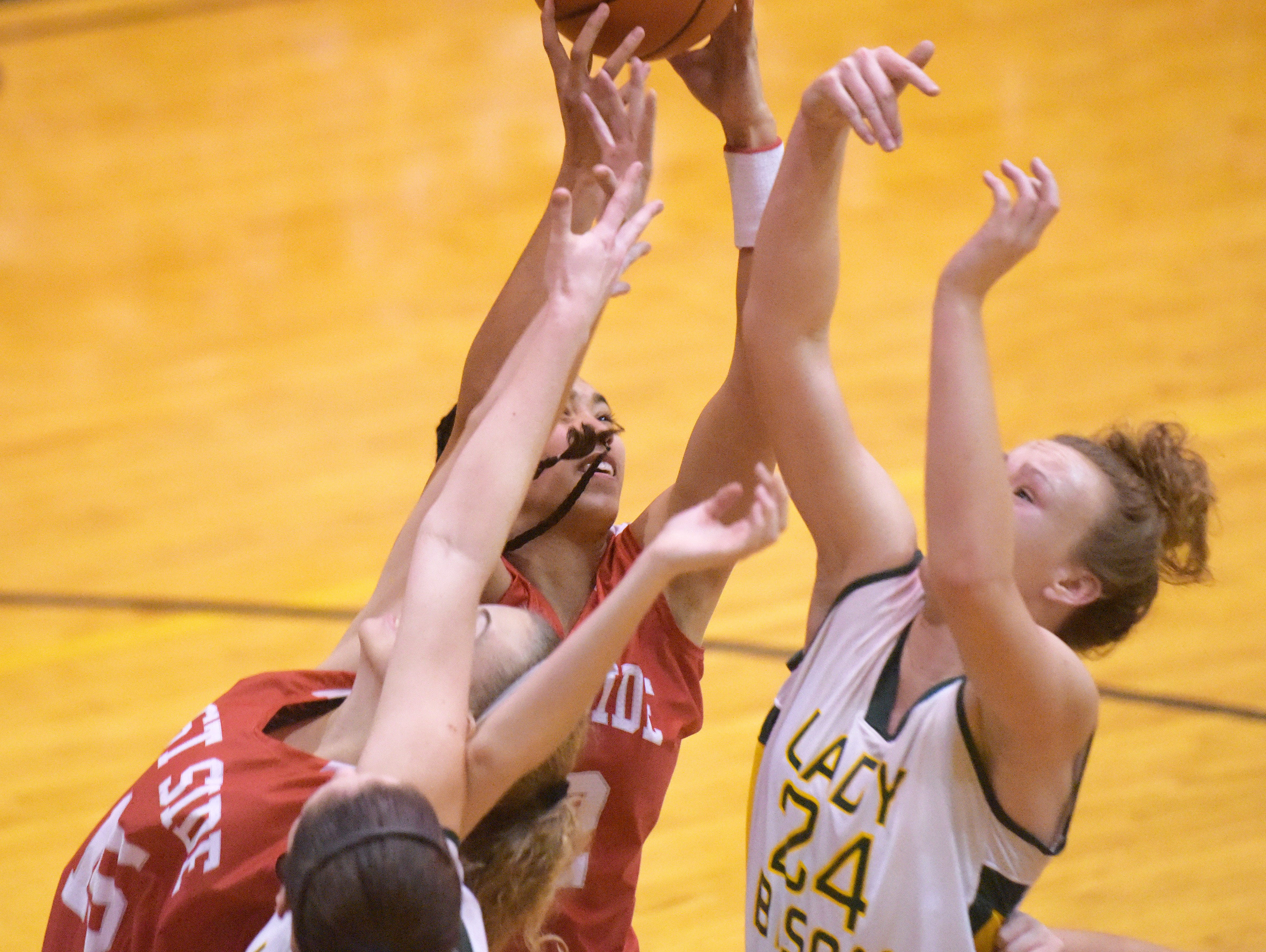 West Lafayette's Kaia Harris, center, goes up for a rebound with Benton Central's Katie Shields Thursday, December 10, 2015 at Benton Central High School. Benton Central was victorious over West Lafayette.