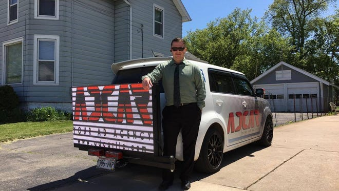 Aaron Alvarado, owner of Ad Car, has rigged a used Scion with a monitor that displays advertising. He plans to traverse Oshkosh, promoting local businesses.