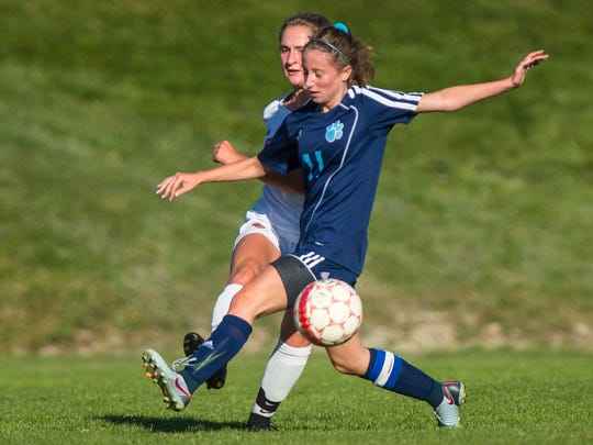 Champlain Valley Union's Sydney Jimmo, left, boots the ball past Mt. Mansfield Union's Fiona Tynion in Hinesburg on Tuesday, October 3, 2017.