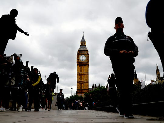 People walk around parliament square on election day in Westminster, London.