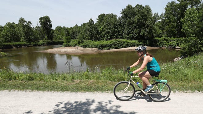 A bicyclist rides toward the Boston Mill Visitor Center on the Towpath Trail past a bend in the Cuyahoga River on Friday June 26, 2020. The National Park Service and U.S. Army Corps of Engineers are reshaping areas of the floodplain adjacent to the Cuyahoga River between the visitor center and Vaughn Road to return the river to a more natural condition.