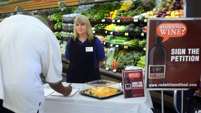 Kroger Lynnwood employee Paula Escue watches as Tim Bryant signs a petition for wine sales in grocery stores in this file photo.