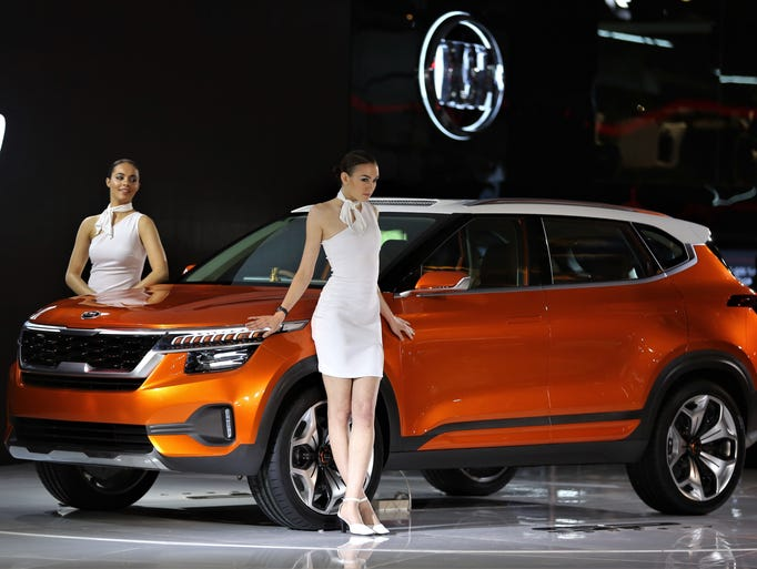 Models pose next to KIA Motors' SP Concept car at the