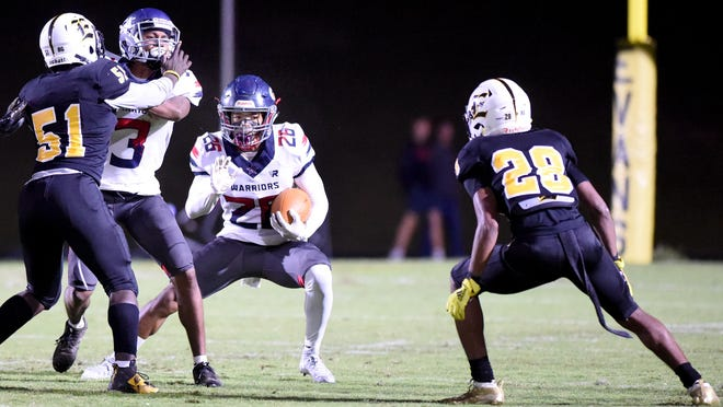 Grovetown's Jose Taylor, middle, ties to elude Evans' Torey Williams, left, and Jalen Walton, right, during football action at Evans High School in Evans, Ga., Friday evening November 8, 2019.
