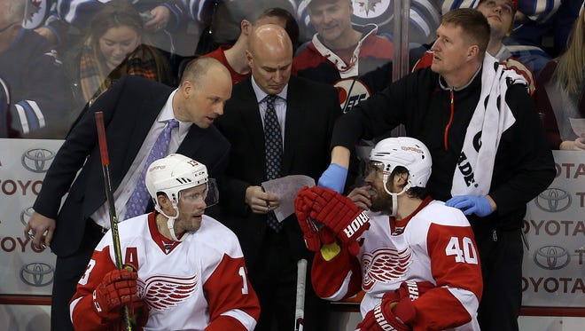Detroit Red Wings coach Jeff Blashill, left,  talks to Pavel Datsyuk (13), and Henrik Zetterberg (40) during the third period of an NHL hockey game against the Winnipeg Jets on Tuesday, Dec. 29, 2015, in Winnipeg, Manitoba.