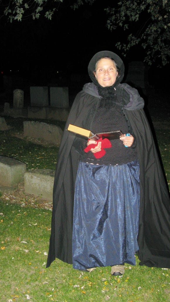 """As we walked through the dark cemetery, friendly """"spirits""""appeared with eerie information on 19th century beliefs and superstitions."""