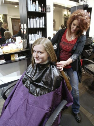 """Olivia McTrusty, 14, gets her hair cut by stylist Robin Braatz of Styles on Boradway. Olivia had not had her hair cut since she was 6 years old. She plans to donate the hair to a charity that provides wigs to children with leukemia. Olivia was featured in the Sheboygan Press when she was 6-years-old while battling childhood leukemia and said the day she got a wig was """"one of the most exciting days of my life."""""""