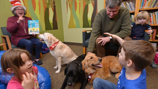 "Sandy Globa, at left, a volunteer with Canine Companions, reads ""What Pet Should I Get,"" by Dr. Seuss, to about 10 children at the Achievement Center in Millcreek Township in 2018. The center will join LECOM Health, pending approval by the Pennsylvania Attorney General's Office"