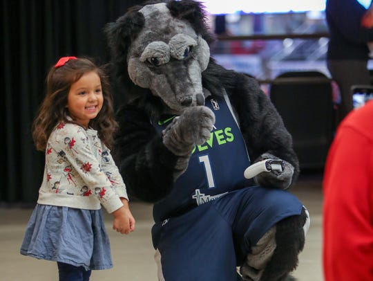 Iowa Wolves mascot, Alpha, poses with a young fan before