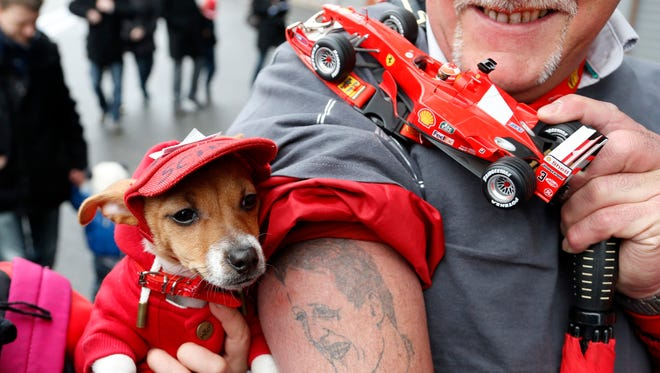 A fan displays a tattoo and a model of a car of seven-times former Formula One world champion Michael Schumacher  during a tribute at the Circuit of Spa-Francorchamps in Belgium on Sunday.