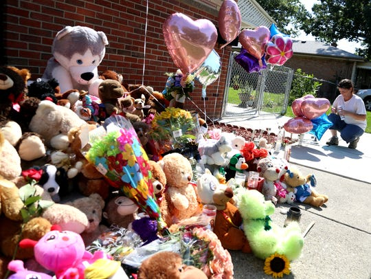 Tonya Ryan, 39 of Allen Park lights a candle to add
