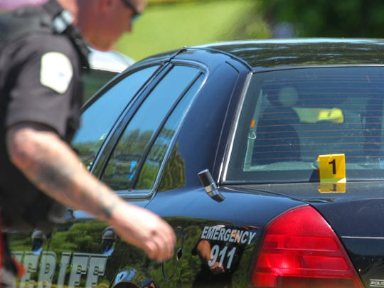 An Anderson County Sheriff's Office deputy looks at an evidence marker on a police cruiser while SLED agents investigate a deputy involved shooting on Lawrence Road just outside Anderson on Tuesday.