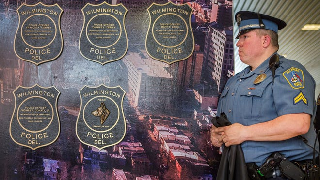 Capitol Police Cpl. Donald Witte, formerly of the Wilmington Police Department, on Friday unveils a memorial plaque for his late K-9 partner, Pietie, at the dedication of a memorial wall honoring city officers killed in the line of duty. Pietie died in 2003 after an on-duty injury.