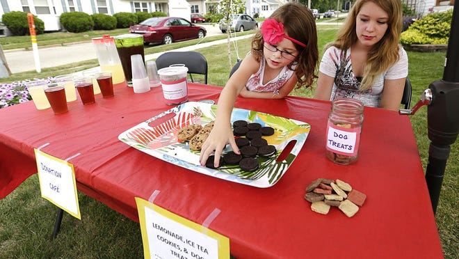 Five-year-old Jaelle Weinberger, of Waupun, straightens out a row of cookies at her lemonade/cookie stand, which she made to raise money for food deprived people in Africa, while her cousin Morgan Linde watches.