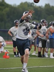 Pittsford quarterback Robby Kleinheimer rolls to his right and throws downfield during practice at Pittsford Mendon High School on Tuesday. Mendon is the third stop on the Democrat & Chronicle's high school football camp tour.