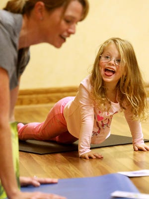Maggie Pape, 4, of East Dubuque, Ill., holds a pose during a toddler yoga class at Body & Soul Wellness Center and Spa in Dubuque.