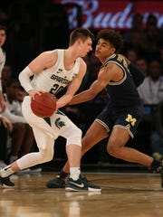 Michigan guard Jordan Poole defends against Michigan State guard Matt McQuaid during second half action of the Big Ten Tournament semifinal Saturday, March 3, 2018 at Madison Square Garden in New York.