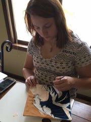 Mikala Bartson paints her graduation cap, which led