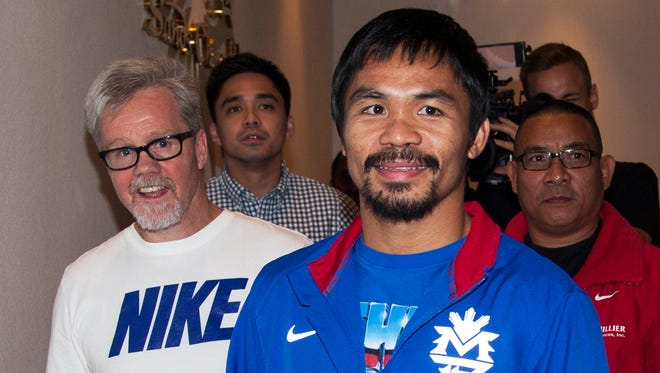 Boxer Manny Pacquiao of the Philippines, shown last week with his trainer Freddie Roach, left,  will visit typhoon-devastated Tacloban in the coming days, as he has promised.