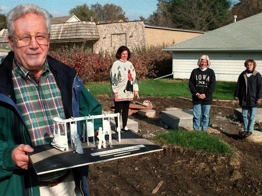 Bill Lawson, left, president of the Downtown Urbandale Neighborhood Association, holds a model of a trolley at the site for Trolley Park in this November 1997 file photo. In the background, from left are Vice President Rebecca Good and board members Debra Jacobs and Dori Fifield.