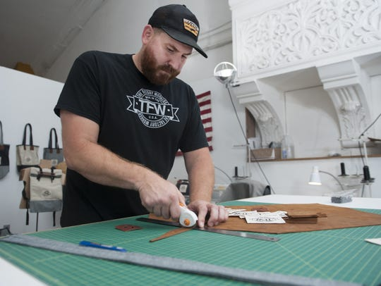 Factory owner Tom Marchetty cuts leather for his line